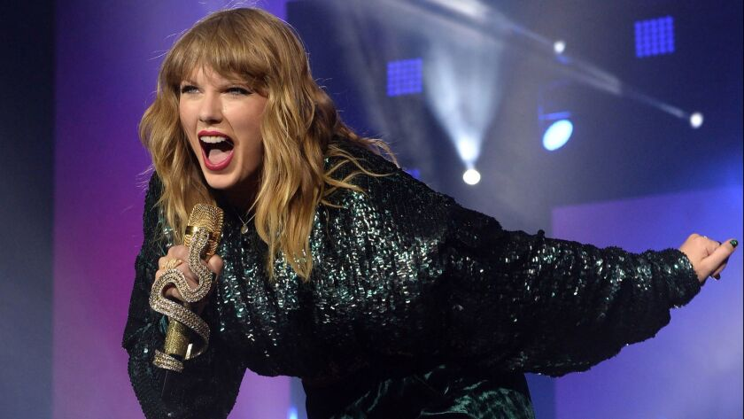 """Taylor Swift, shown performing in London in 2017, has sparked a fierce social media debate over her new version of Earth, Wind & Fire's 1978 hit """"September."""""""
