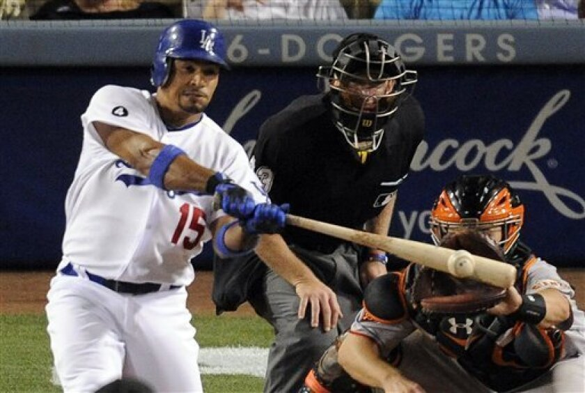 Los Angeles Dodgers' Rafael Furcal, left, hits an RBI single as San Francisco Giants catcher Buster Posey, right, catches as umpire Lance Barksdale looks on during the sixth inning of their Major League Baseball game, Friday, April 1, 2011, in Los Angeles. (AP Photo/Mark J. Terrill)