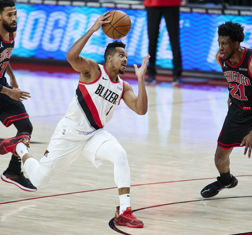 Portland Trail Blazers guard CJ McCollum, center, drives to the basket between Chicago Bulls guard Garrett Temple, left, and forward Thaddeus Young, right, during the first half of an NBA basketball game in Portland, Ore., Tuesday, Jan. 5, 2021. (AP Photo/Craig Mitchelldyer)