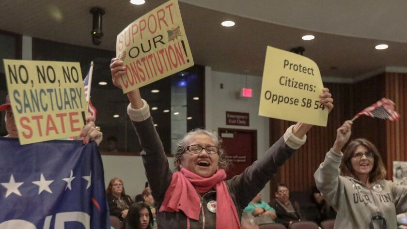 "At the Orange County Board of Supervisors meeting, people opposing California's ""sanctuary"" law celebrate."