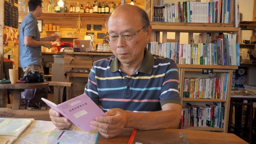Kazuhiko Futagawa looks at a medical booklet that shows he is entitled to free healthcare, since he