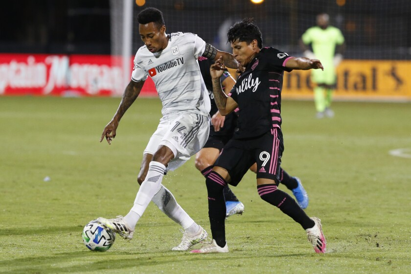 Seattle Sounders forward Raul Ruidiaz and LAFC midfielder Mark-Anthony Kaye compete for the ball.