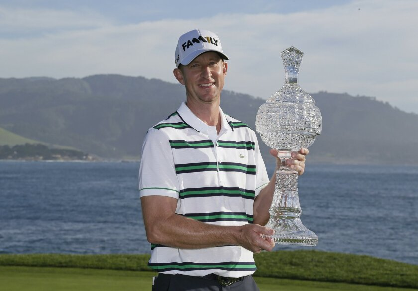 Vaughn Taylor poses with his trophy on the 18th green of the Pebble Beach Golf Links after winning the AT&T Pebble Beach National Pro-Am golf tournament Sunday, Feb. 14, 2016, in Pebble Beach, Calif. (AP Photo/Eric Risberg)