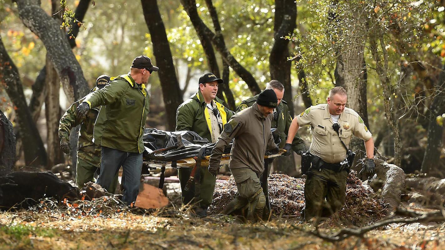 Agentes del Sheriff cargan un cuerpo entre las puedras y el lodo, cerca de Hot Springs Road, en Montecito, después de que una gran tormenta azotó un área que días antes se había incendiado.