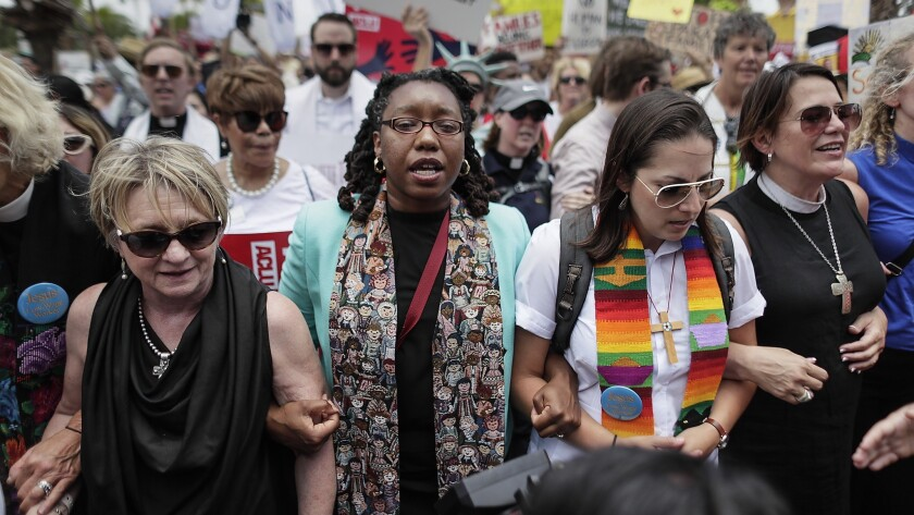 BROWNSVILLE, TEXAS, THURSDAY, JUNE 28, 2018 - A group of clergy lock arms and advance toward the Re