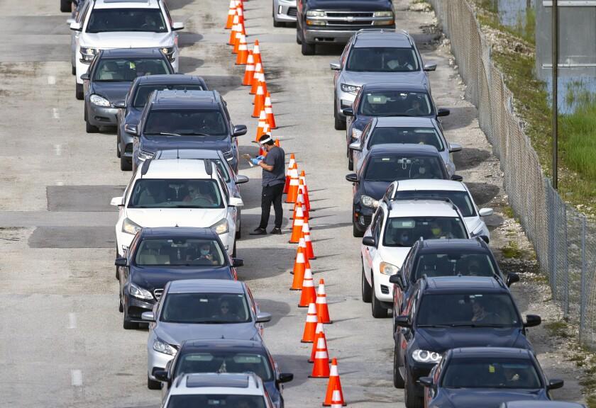 Vehículos forman una fila al tiempo que personal sanitario llena un formulario sobre pruebas de COVID-19 en el centro de pruebas en el Estadio Hard Rock de Miami Gardens, Florida, el miércoles 28 de octubre de 2020. (David Santiago/Miami Herald via AP)