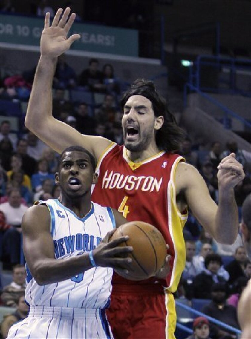 New Orleans Hornets guard Chris Paul, left, goes to the baske ahead of Houston Rockets forward Luis Scola (4) in the first half of an NBA basketball game in New Orleans, Saturday, Jan. 2, 2010. (AP Photo/Bill Haber)