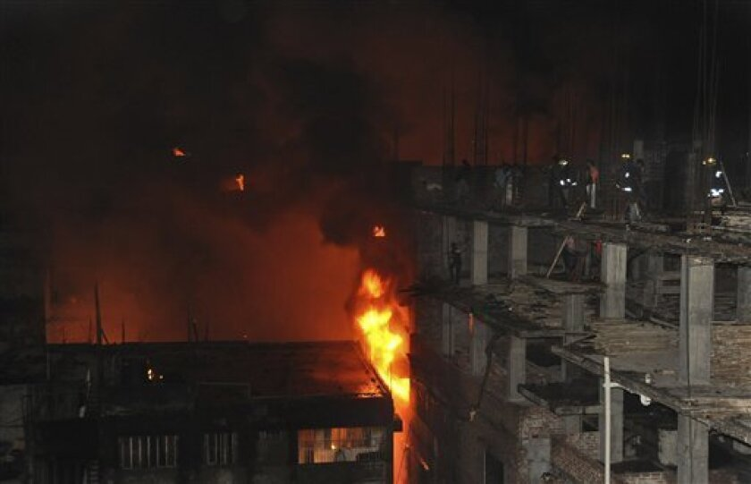 People seen on an adjacent building try to extinguish a fire in Dhaka, Bangladesh, Thursday, June 3, 2010. Authorities say the fire in the Bangladeshi capital has killed at least three people and injured dozens more. Fire official Abdus Salam says the blaze started late Thursday after an electric transformer exploded, igniting a three-storey apartment building. (AP Photo/Khorshed Alam)