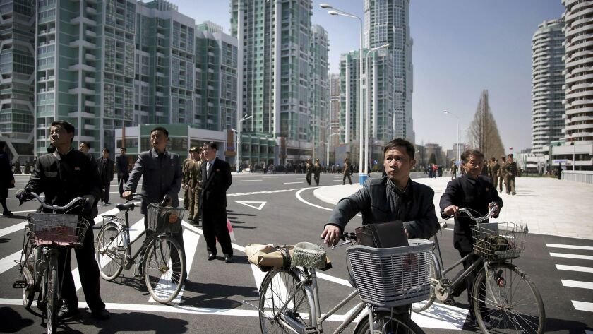 North Korean men push their bicycles along Ryomyong residential area, a collection of more than a do