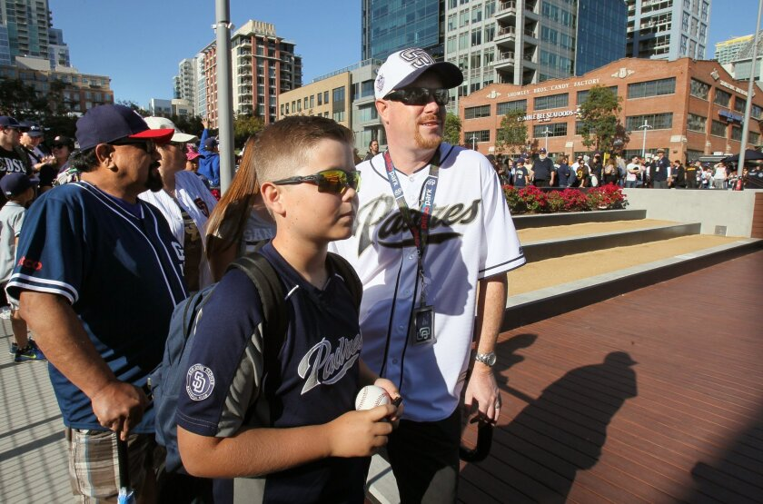 Grant Featherston and his son Drew, 11, wait in line for Padres autographs prior the exhibition game with the White Sox.