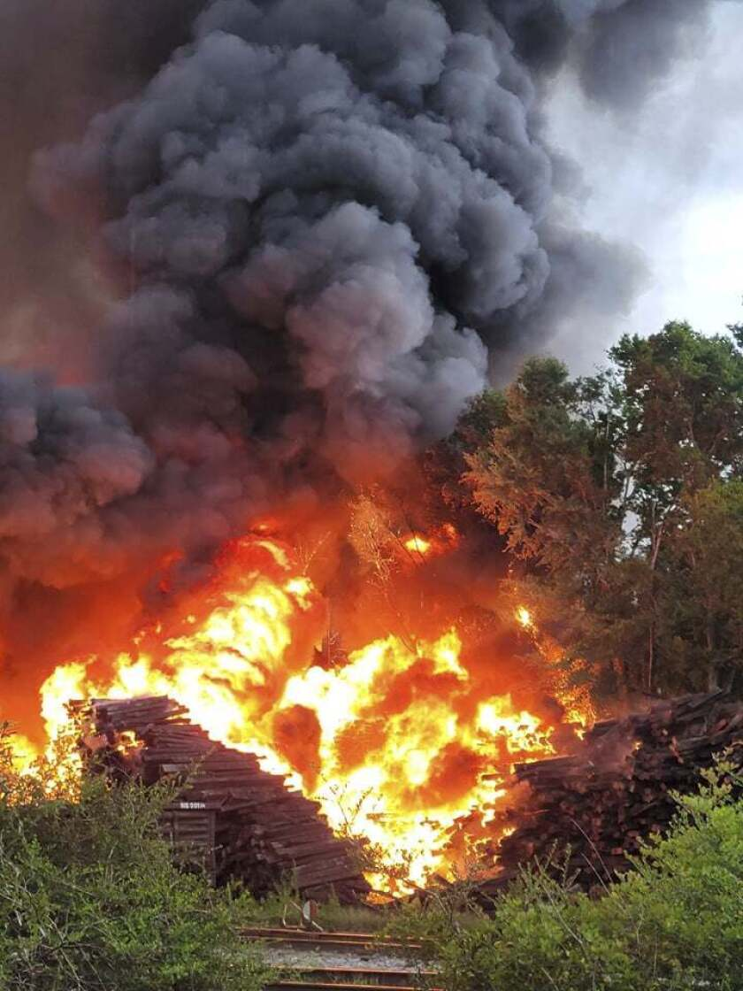 Smoke and fire fill the air from a blaze at National Salvage and Services Corp., on Monday, Aug. 2, 2021 near Selma, Ala. The fire that apparently started with a lightning strike and grew so large it showed up on weather radar engulfed a pile of thousands of railroad ties at a recycling plant in rural west Alabama. (Lane Frazer via AP)