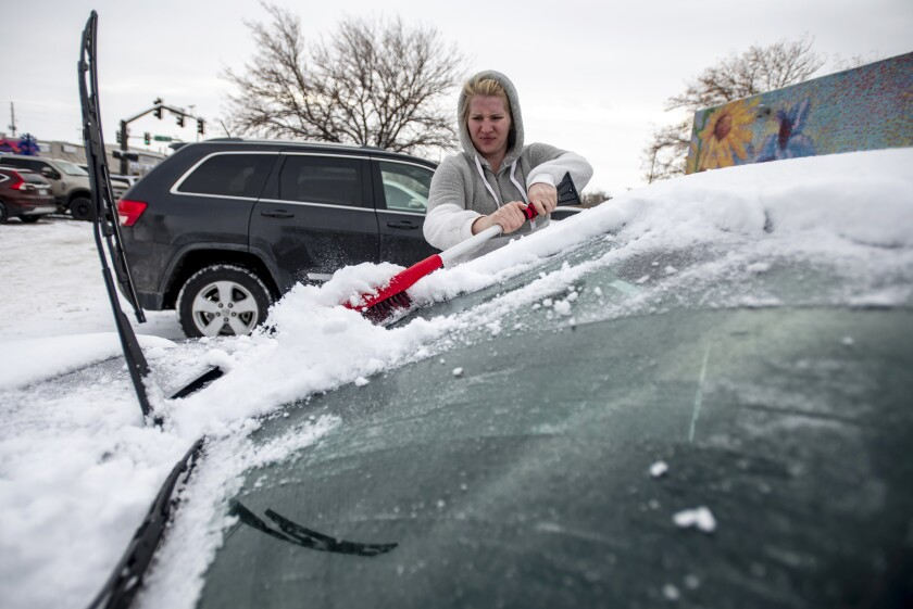 Brittany Culp scrapes snow off her windshield Saturday in Greeley, Colo.