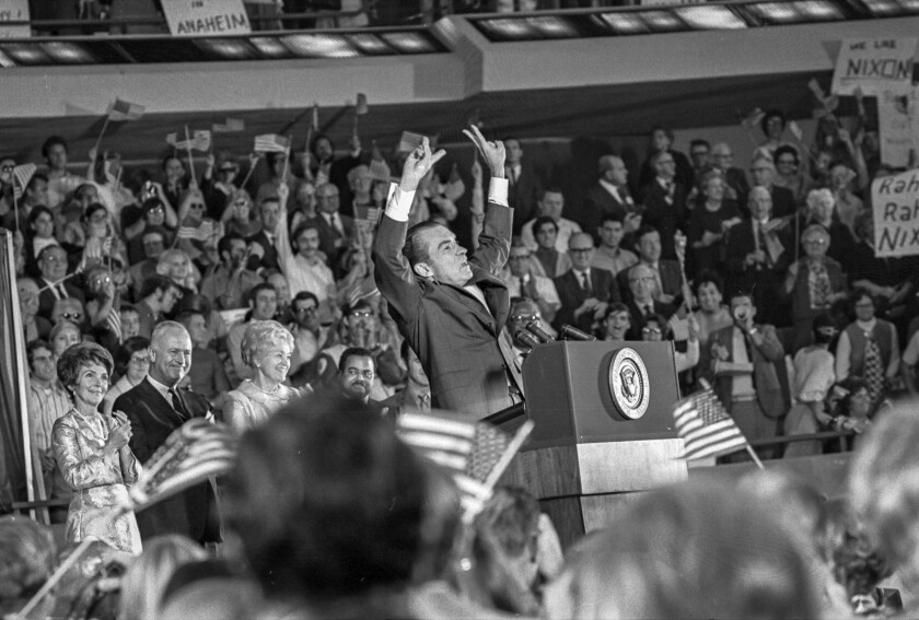 Oct. 30, 1970: President Nixon raises his arms in a V for victory gesture as he addresses a rally at the Anaheim Convention Center. Also on the platform is Nancy Reagan, at left.