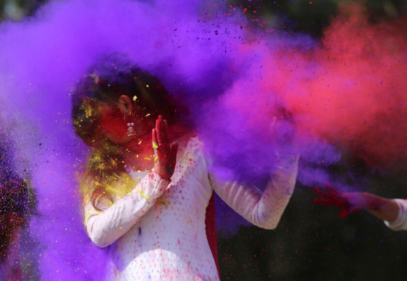 Indian college girls throw colored powder to one another during Holi festival celebrations in Bhopal, India.