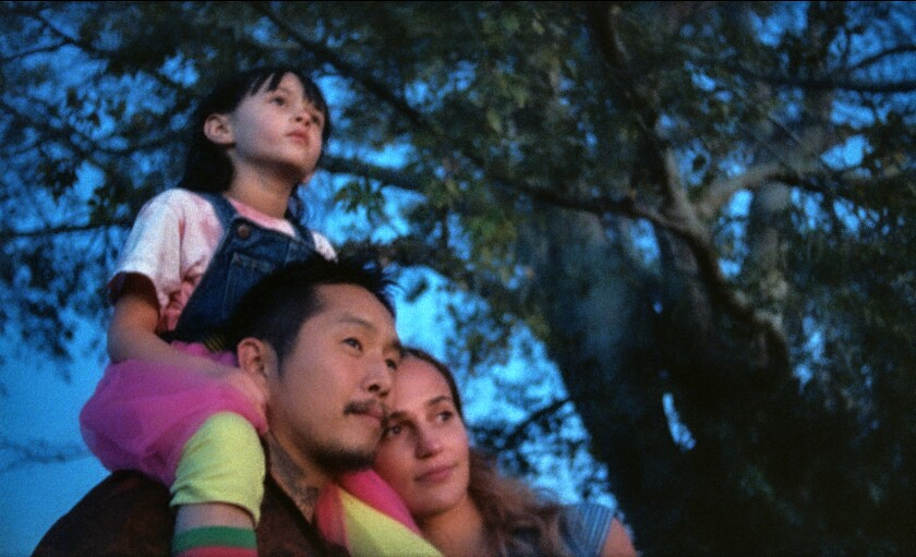 """A man, with a child on his shoulders, and a woman stand in front of a tree in the movie """"Blue Bayou."""""""