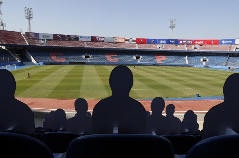 Cutouts of soccer fans sit in the bleachers of the Cerro Porteno
