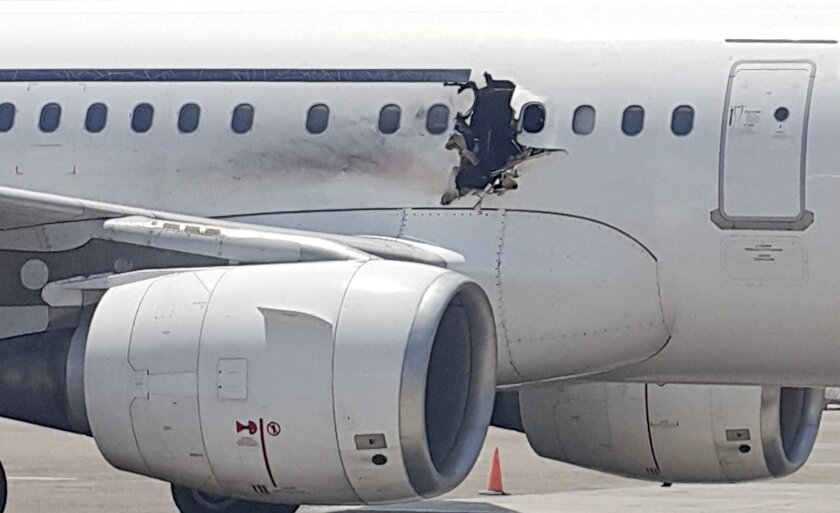 FILE - In this Tuesday, Feb. 2, 2016 file photo, of a  hole in a plane operated by Daallo Airlines as it sits on the runway of the airport in Mogadishu, Somalia. A military court in the Somali capital has given life terms Monday, May 30, 2016 to two men convicted of masterminding the bombing in Feb