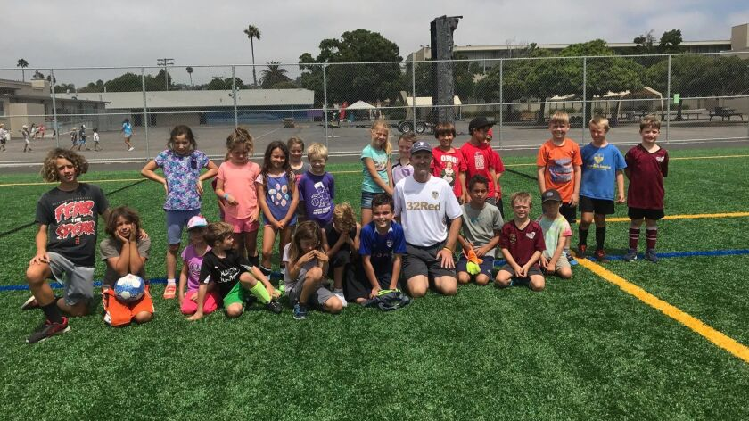 YMCA director Mike Roberts (front and center) poses with the soccer players he coaches.