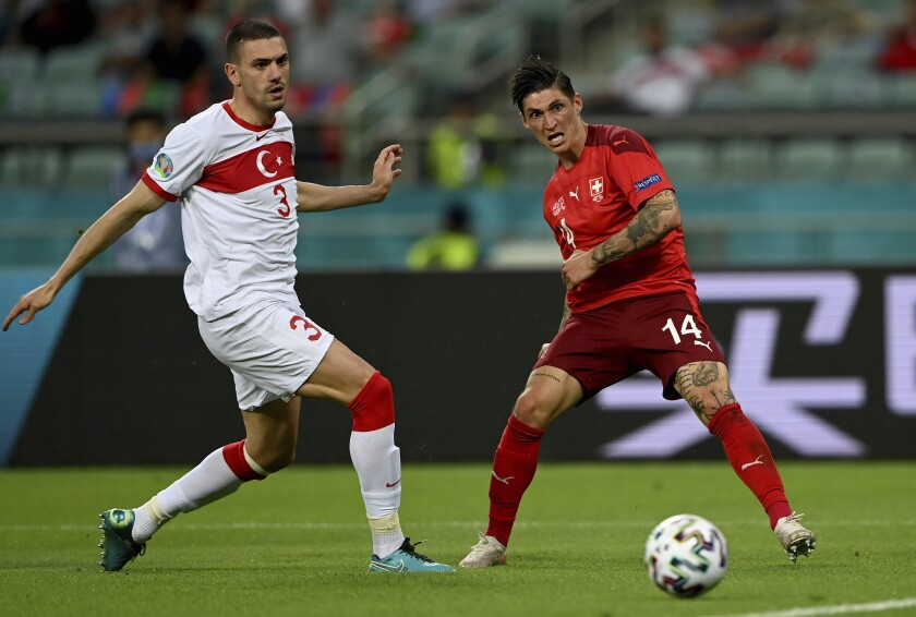 Turkey's Merih Demiral, left, and Switzerland's Steven Zuber challenge for the ball during the Euro 2020 soccer championship group A match between Switzerland and Turkey at the Baku Olympic Stadium in Baku, Azerbaijan, Sunday, June 20, 2021. (Ozan Kose/Pool via AP)
