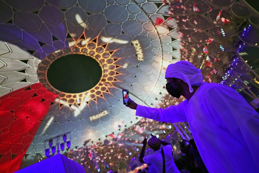 A man takes selfie under the dome of Al Wasl Plaza coloured in French national flag, during a French ceremonial day at the Dubai Expo 2020 in Dubai, United Arab Emirates, Saturday, Oct. 2, 2021. (AP Photo/Kamran Jebreili)