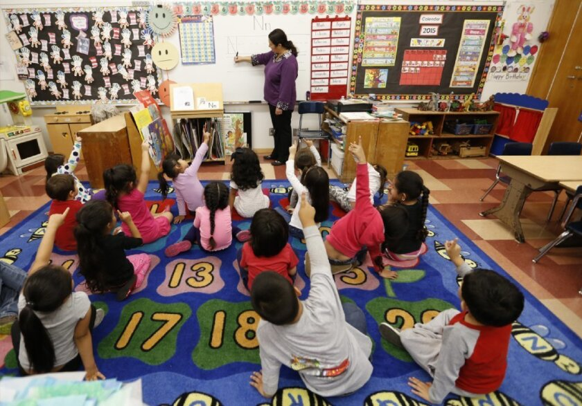 Students raise their hands in a pre-kindergarten classroom.