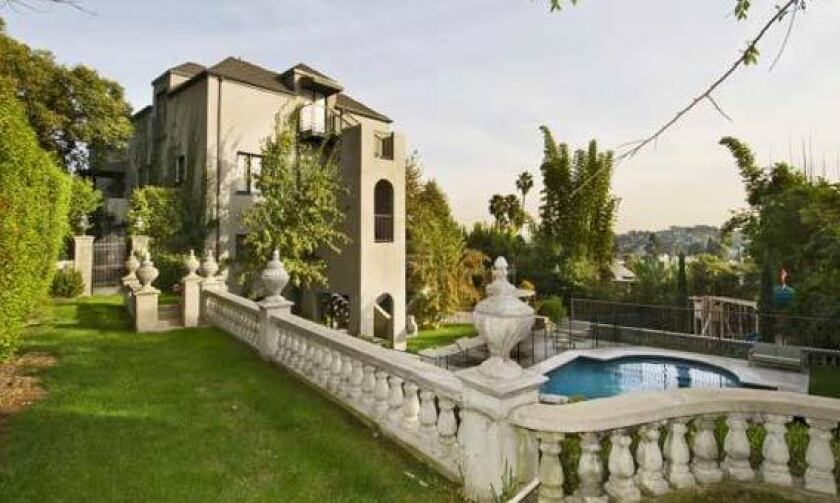 The stately three-story Mediterranean, built in 1922, overlooks the pool and yard and has city views.