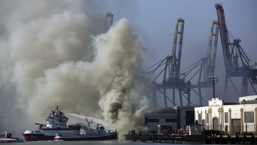 A plume rises from a stubborn fire at the Port of Los Angeles that continues to burn World War II-era lumber pylons soaked in creosote, prompting air quality concerns Tuesday.