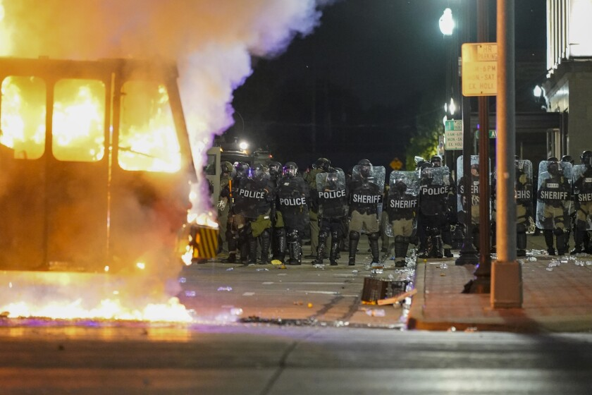 FILE - In this Aug. 24, 2020 file photo, police stand near a garbage truck ablaze during protests over the shooting of Jacob Blake in Kenosha, Wis. In the span of 48 hours, two Black men in U.S. cities hundreds of miles apart were shot by police in episodes that set off a national conversation about the need for officers to open fire on people walking away from them. (AP Photo/Morry Gash, File)