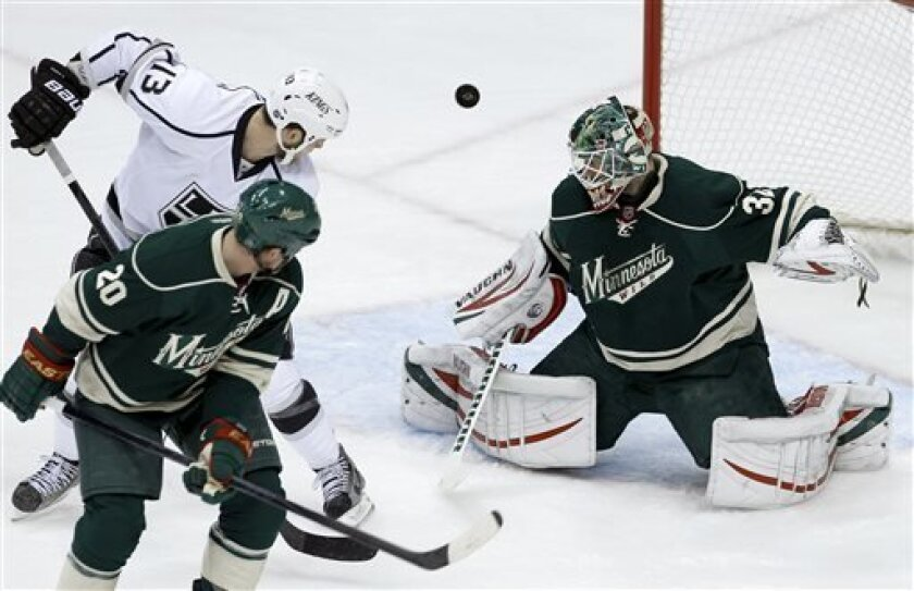 Minnesota Wild goalie Niklas Backstrom right, of Finland, deflects a shot by Los Angeles Kings left wing Kyle Clifford (13) as Wild defenseman Ryan Suter (20) watches during the first period of an NHL hockey game in St. Paul, Minn., Saturday, March 30, 2013. (AP Photo/Ann Heisenfelt)