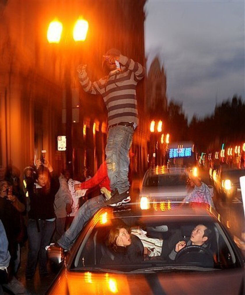 Motorists in Oakland, Calif., react as demonstrators jump on their car following the sentencing of Johannes Mehserle on Friday, Nov. 5, 2010. Mehserle, a former police officer who fatally shot unarmed black man Oscar Grant on New Year's Day 2009, received a two year prison sentence. (AP Photo/Noah Berger)