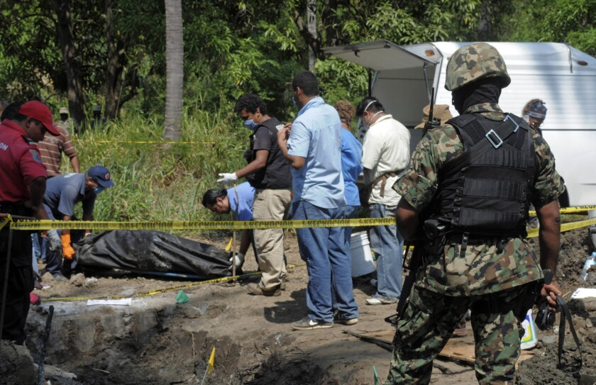 Un miembro dela Marina de México observa los trabajos de empleados del servicio médico forense en Tuncingo, México. Numerosas fosas clandestinas han sido encontradas por todo el territorio mexicano. (AP)