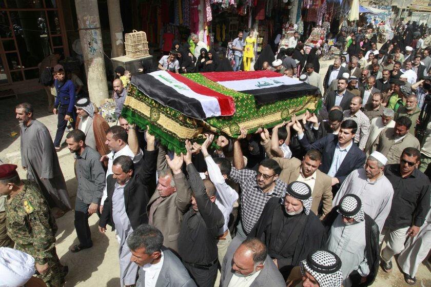 Mourners carry a coffin draped with Iraqi flags during the funeral procession for Shaima Alawadi. (AP Photo/Hadi Mizban).