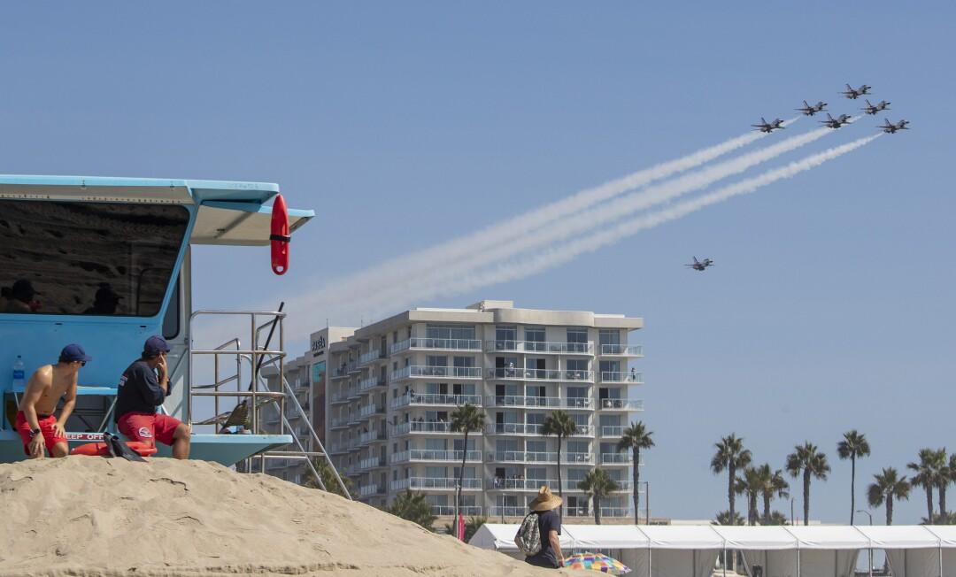 A Huntington Beach lifeguard plugs his ears as the U.S. Air Force Thunderbirds arrive