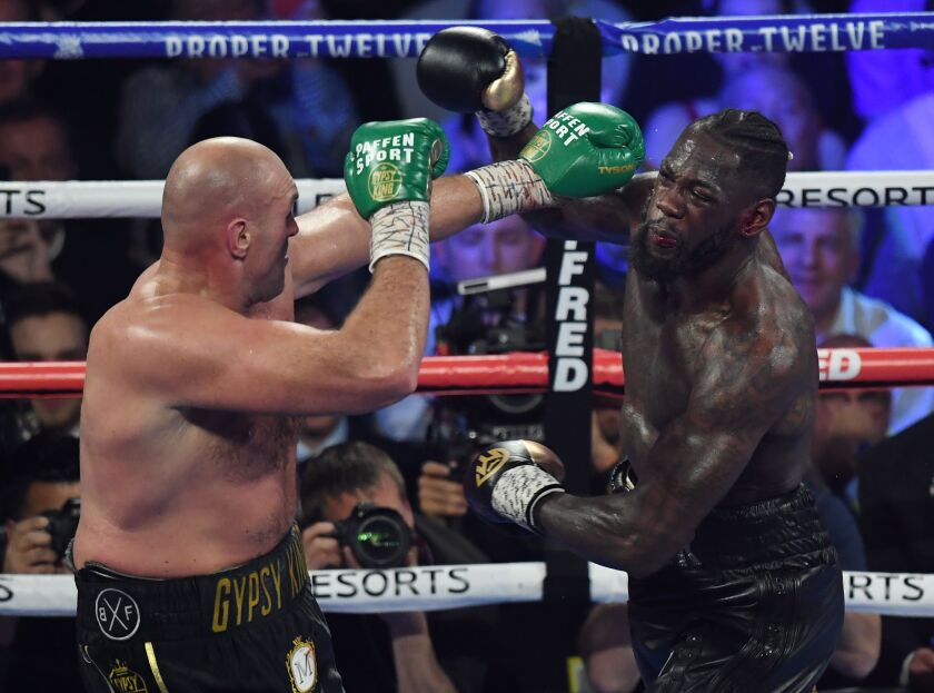 Tyson Fury, left, and Deontay Wilder exchange punches during their heavyweight title fight in Las Vegas on Feb. 22.