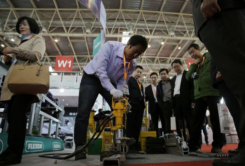 In this Oct. 30, 2015 photo, an exhibitor, center, demonstrates a machine to the visitors at his company's booth during the China Coal & Mining Expo in Beijing, China. President Xi Jinping said Tuesday, Nov. 3, 2015 that China needs at least 6.5 percent economic growth in coming years and the Commu