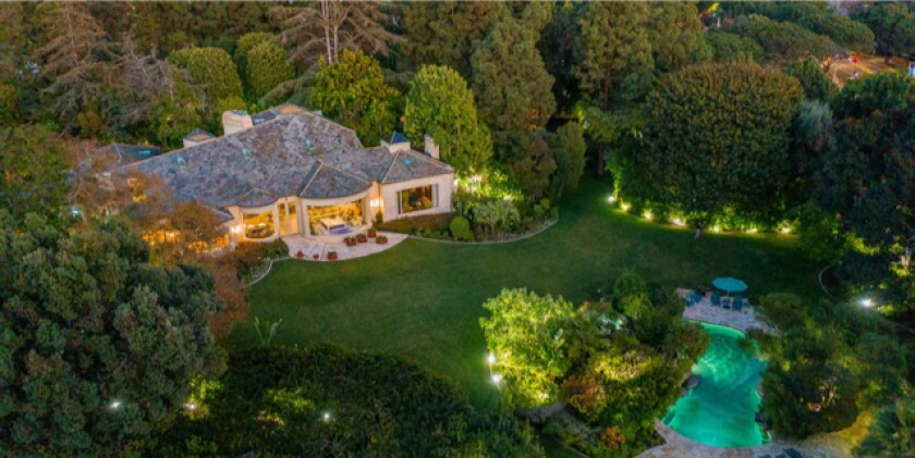 The 2.5-acre estate holds a swimming pool, tennis court and French country-style home