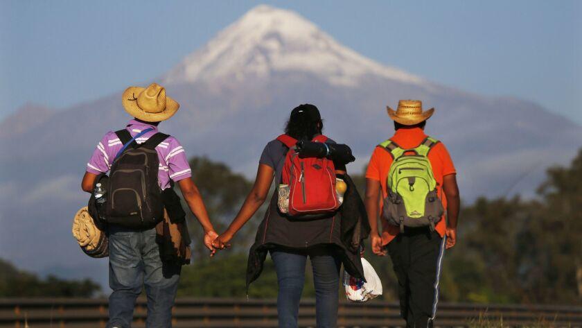 Central American migrants begin their morning trek facing Pico de Orizaba volcano as part of a thous