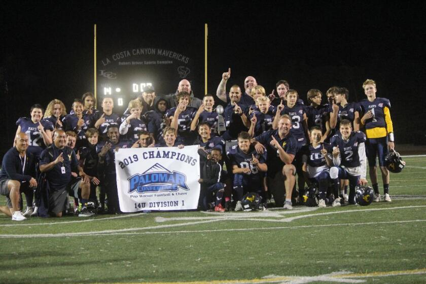The La Costa Canyon Mavericks Division 1 14U team and coaching staff holding up the 2019 Palomar Conference Pop Warner Football Champions banner and displaying their game rings.