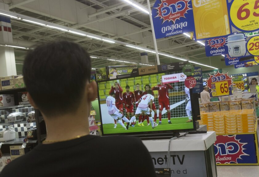 "A Thai shopper watches a soccer match on a flat-panel television at a shopping mall in Bangkok, Thailand Wednesday, June 11, 2014. Thailand's military junta, which promised to ""return happiness to the people"" after last month's coup, has asked regulatory officials to find a way to allow the country's many soccer fans to watch all of the 2014 World Cup for free. (AP Photo/Sakchai Lalit)"