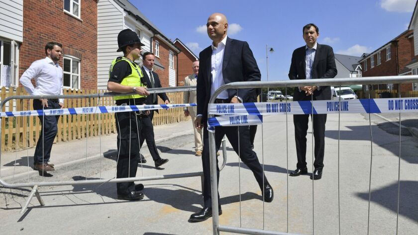 Britain's Home Secretary Sajid Javid, center, exits the police cordon at Muggleton Road where counter-terrorism officers are investigating a couple's exposure to the nerve agent Novichok in Amesbury, England, on Sunday.