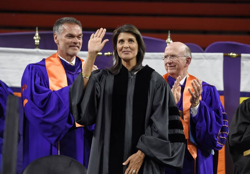 FILE - In this May 10, 2018 file photo, Clemson board of trustees members, William C. Smith, left, and David H. Wilkins applaud while UN Ambassador Nikki Haley, a 1994 Clemson graduate, waves to the crowd before she gives the 2018 Commencement speech in Clemson, S.C. As she ponders her next political steps, Haley has accepted a lifetime appointment to the the Board of Trustees of Clemson University, her alma mater. The university made the announcement on Tuesday, Oct. 12, 2021. (AP Photo/Richard Shiro, File)