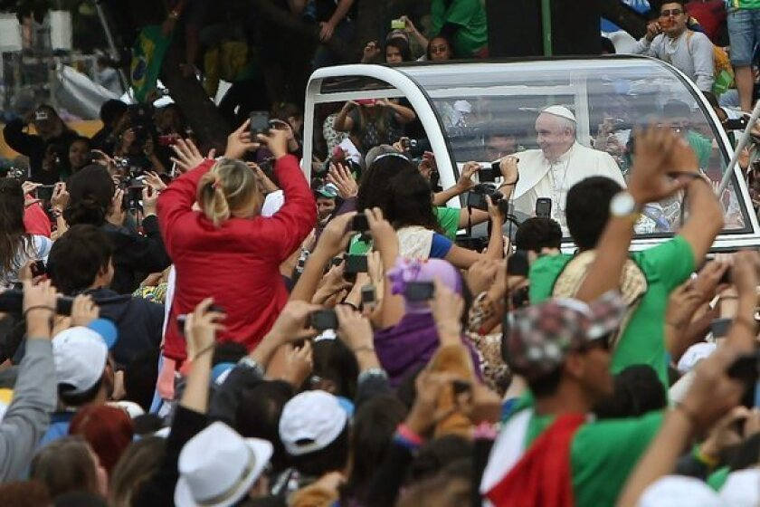 Pope Francis is mobbed by young pilgrims upon his arrival to Copacabana beach in Rio de Janeiro.