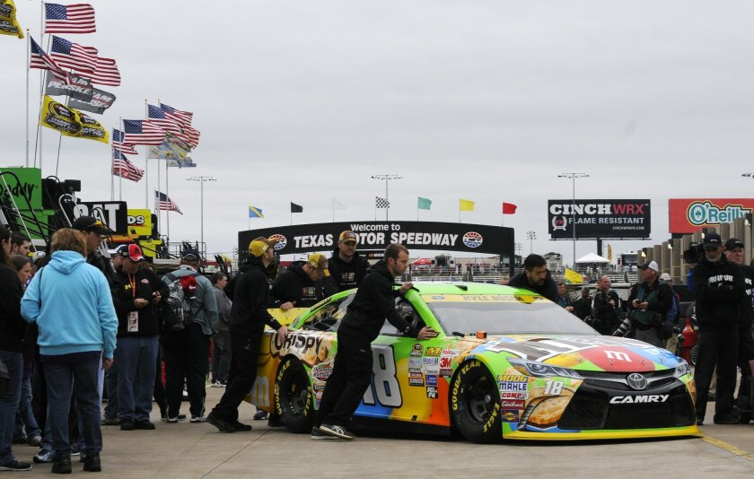 The crew for Sprint Cup Series driver Kyle Busch roll his car in the garage area while waiting out a NASCAR auto race weather delay at Texas Motor Speedway Saturday, Nov. 7, 2015, in Fort Worth, Texas. The morning and afternoon Sprint Cup Series practice session were canceled. (AP Photo/Ralph Lauer