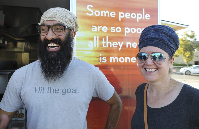 Davinder Singh and his wife Harisimran Khalsa, shown standing in front of a food trailer they launched last year, are nearing their fundraising goal to create mobile showers for homeless people in San Diego County.