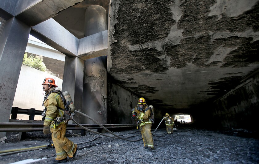 Los Angeles city firefighters pull hoses out of the connector tunnel between the 2 and 5 freeways that was heavily damaged when a big rig flipped and burned in July.