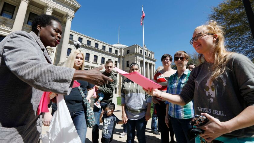 """Patricia Ice, left, an attorney with the Mississippi Immigrants Rights Alliance, hands out fliers at the Capitol in Jackson, Miss., that call for the freeing of Daniela Vargas, a """"Dreamer"""" detained by immigration authorities."""