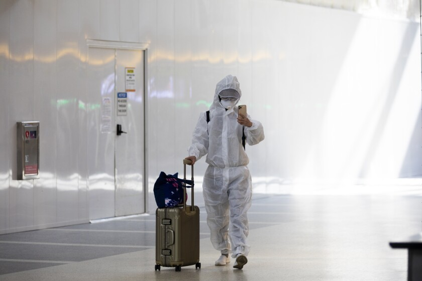 A passenger wearing personal protective equipment walks in the Tom Bradley International Terminal at LAX on November 17.