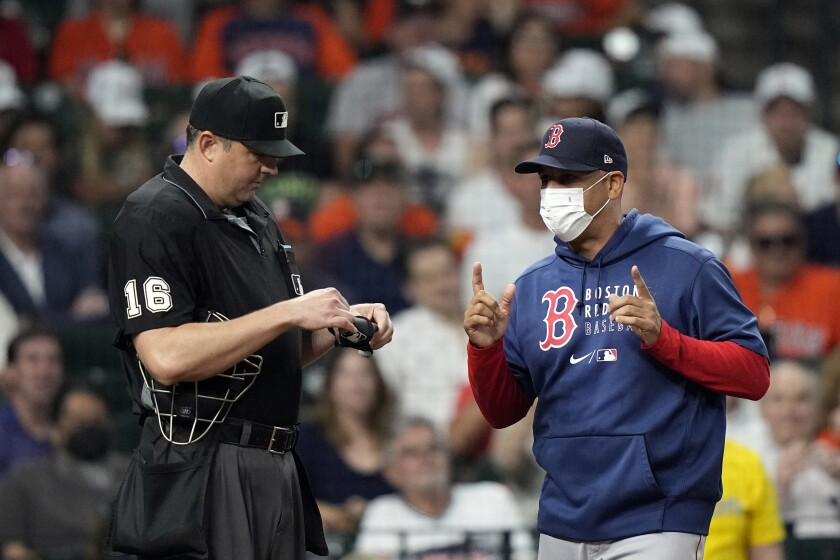 Boston Red Sox manager Alex Cora, right, argues strike calls with home plate umpire Lance Barrett during the sixth inning of a baseball game Thursday, June 3, 2021, in Houston. (AP Photo/David J. Phillip)