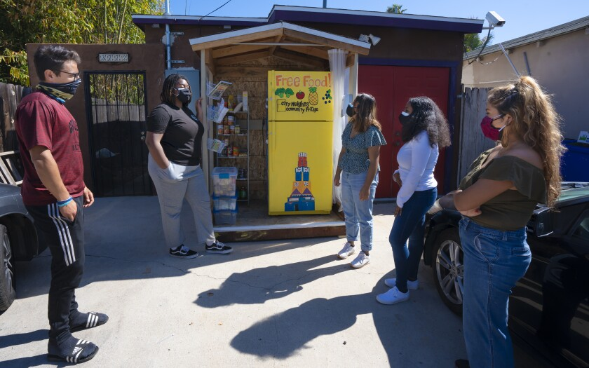 Five organizers and residents view a yellow community fridge in City Heights that has a Free Food sign on it.