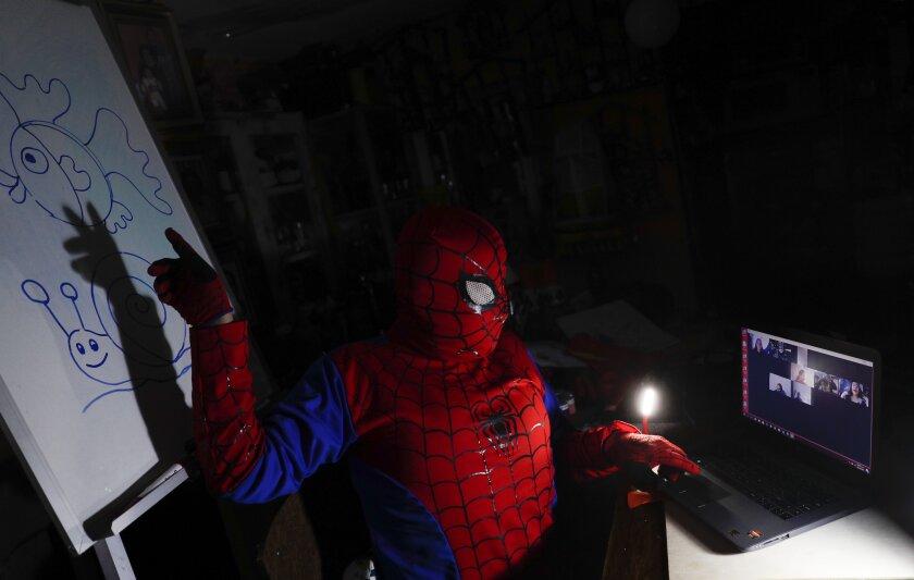 Art teacher Jorge Manolo Villarroel, wearing a Spider-Man costume, teaches an online class from his home, amid the new coronavirus pandemic in La Paz, Bolivia, Tuesday, June 9, 2020. Villarroel, who lives in a poor neighborhood of the capital, teaches art at the San Ignacio Catholic School in a wealthier area of the city. (AP Photo/Juan Karita)